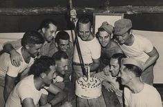 """""""Victory Carving-First Division Marines on Okinawa gather around Corporal John Dulin as he wields a Japanese samurai sword to cut a VJ cake that he baked for the celebration. That isn't sugar cake though, the icing is made of starch."""""""