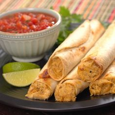 Cheesy chicken taquitos on plate with salsa and lime