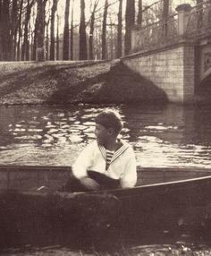 """Tsarevich Alexei Nikolaevich Romanov of Russia in a boat in the Alexander Park canals at Tsarskoe Selo. """"AL"""""""