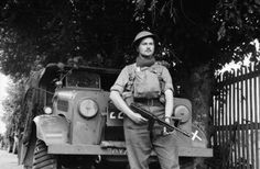 A soldier of the 52nd Lowland Division poses with his Thompson sub-machine gun and a Bedford MWD truck in France, 13 June 1940.