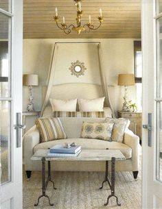 love the faux canopy treatment and the sofa/table arrangement at foot of bed