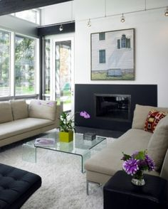 Contemporary living room - shag rug; artwork over fireplace; honed black granite fireplace surround; black chair and side table by annabelle