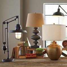 Jennison Table Lamp | The smooth, rounded curves of this matte black iron lamp lend it an air of modern, artistic flair which is accentuated when paired with the contracting natural fabric shade.