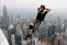 A base jumper leaps backwards off the Menara Kuala Lumpur Tower, Malaysia, Wednesday, Oct. 28, 2009. A group of base jumpers were attempting to set a Guinness World Record striving to have 24 people base jump every hour for 24 hours from the the 915 feet high communication tower.
