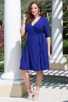 You've found it! Our plus size Essential Wrap Dress is everything a signature cocktail dress should be: slimming lines, a flattering tie and a fluid knee-length skirt. Shop made in the USA styles at www.kiyonna.com. #kiyonna #bluedress #wrapdress