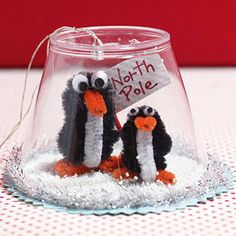 Christmas Craft Ideas: Penguin Snow Globe. How to make it: make your pipecleaner penguins. Then get your plastic cup and put it on a piece of fancy paper. Make your north pole sign and your DONE!!!!