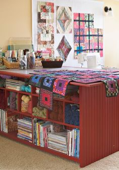 Sewing room: cutting table with storage on both sides; design wall.