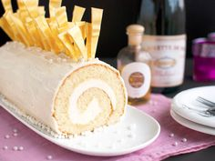 Filled with Champagne buttercream and decorated with gold chocolate shards and sugar pearls, this cake roll is the pinnacle of festivity. Instead of using ordinary Champagne, I make this cake with Marc de Champagne, a pomace brandy made from Champagne grape skins, seeds, and stalks that pairs beautifully with the cake's creamy buttercream filling and sweet white chocolate ganache coating.