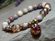 About the Bracelet It's hard to take your eyes off this beautiful Swarovski crystal charm. Rose Terra Jasper adds a subtle touch to this beautiful bracelet that is hard to resist. Bracelet Details: Th