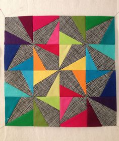 """Wonky Pinwheel"" block by Maureen Kelly. Love the brights against this grey background."