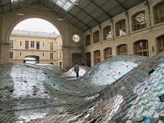 "Waste Landscape: ""Elise Morin (artist) and Clémence Eliard (architect) of SMALL MEDIUM LARGE -SML - design studio, in collaboration with the 104.fr have collected, sorted and hand-sewn 65,000 CDs and turned them into rolling hills of shiny aluminium that command the space of the Centquatre at the Halle d'Aubervilliers in Paris, a building which has been refurbished by atelier Novembre: Marc Iseppi & Jacques Pajot."""