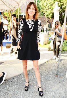 Alexa Chung wears a printed blouse, black pinafore dress, and platform sandals