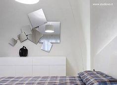 Conjunto desordenado de espejos cuadrados en la pared de un dormitorio.