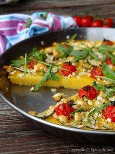 Polenta grillée aux tomates cerises, courgettes et feta 4 personnes / moule Ø 30 cm ✓ 375 g de polenta instantanée ✓ 1,3 l d'eau bouillante ✓ 200 ml de vin blanc ✓ 1 cube de bouillon de légumes ✓ 2 càs de beurre végétal ✓ 2 càs pleines de parmesan fraîchement râpé ✓ Une douzaine de tomates cerises ✓ 1/2 courgette ✓ 1 oignon nouveau ✓ 100 g de feta ✓ Sel et poivre noir du moulin ✓ 2 à 3 càs d'huile d'olive ✓ Quelques feuilles de basilic au goût ✓ Quelques feuilles de roquette