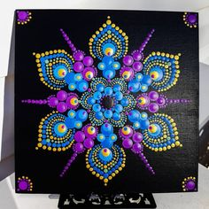 Beautiful dot mandala on black canvas board in purple, gold and blue.Angelikamadethis by AngelikaMadeThisImage gallery – Page 58898707612441182 – Artofit Dot Art Painting, Rock Painting Designs, Mandala Painting, Stone Painting, Canvas Painting Patterns, Mandala Art Lesson, Pottery Painting, Painting Canvas, Mandala Painted Rocks