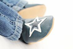 Navy leather shoe with a white star design and a tan suede sole.  These baby shoes are made from soft leather and have suede soles with elasticated ankles so that they fit really well and don't keep falling off - no more lost socks!!  Ideal for wooden and laminated floors due to their non-slip suede soles.  These shoes would be the perfect present for any little boy, as they come in a golden organza drawstring bag. (See picture 4)  They'll fit through your letterbox so they are easy to…