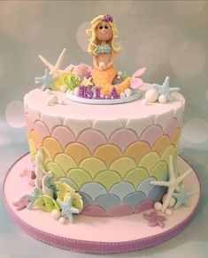 Mermaid birthday celebration cake with pastel rainbow scale design and starfish and coral. The topper is made from clay