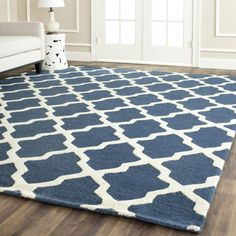 Add an exotic touch to your home with this handmade wool area rug by Safavieh, with a Moroccan-inspired ivory design against a navy blue background. Hand-tufted with 100 percent wool and backed with cotton canvas, this rug spans 11 feet by 15 feet.