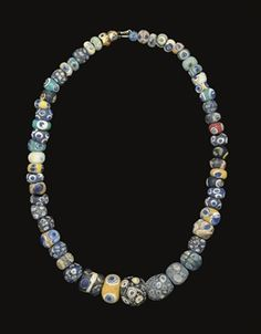 A PHOENICIAN GLASS EYE BEAD NECKLACE  CIRCA 6TH-2ND CENTURY B.C.  Composed of fifty-seven globular beads, in various shapes and sizes, dark blue, yellow, turquoise and green in color, with compounded eyes blue on white; strung on a cord 18 in. (45.7 cm.) long