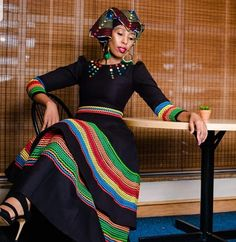 Clipkulture - The Best Wedding Planner for Traditional Wedding Decor! Zandi in black flare umbhaco dress with colourful embroidery patterns. Crowned with colourful designed Doek and earrings. Outfit by Scripture. South African Dresses, Latest African Fashion Dresses, African Print Fashion, Africa Fashion, African Attire, African Wear, African Lace, African Prints, Sepedi Traditional Dresses
