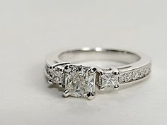 Elegant in design, this petite diamond engagement ring showcases ten round pavé-set diamonds with two princess-cut side diamonds and your diamond of choice set in 14k white gold. Setting includes 1/3 carat total diamond weight. #bluenile