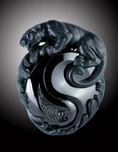 "Jadeite Artist Junyi Wang - A BLACK JADEITE CARVING, BY WANG JUNYI The opaque black jadeite, realistically carved as a panther clambering on a Daoist yinyang symbol surrounded by scroll motifs, representing the rebus ""bao ping an"" or ""Wishing you a safe and peaceful life"", carving approximately 50.80 x 40.46 x 15.26 mm"