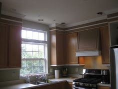 She is in the process of filling the gap between the the top of the cabinets and the ceiling.  See how she put 2 separate bits of trim.  One small piece at top edge of cabinet, on the in the middle, and on crown at top.