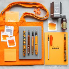 An orange and grey inspired flat lay of fountain pens, notebooks, and ink.