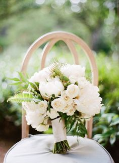 Bride's all white bouquet of peonies and roses with fern accent