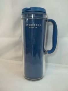Tall, thin travel mug with handle and flip top. Scratches fron normal use and tab on flip top is stained from coffee.