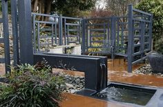 """Love: water feature, """"fence"""", rocks, and dyed concrete surface. The main """"don't like"""" is that my husband wants something more """"natural"""". I'd want a real firepit (there is a free standing fire place in the corner) but be thrilled to walk outside and find this."""