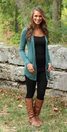 Teal cardigan over all black with tan boots.