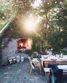 Un coin repas installé près d'une cheminée extérieure