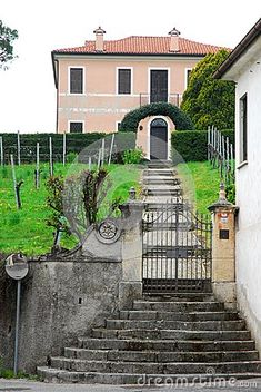 Photo made at the entrance of a house in Breganze in the province of Vicenza in Veneto (Italy). In the picture you see, in the foreground, the staircase, the entrance gate with the small walls and columns that support it. Beyond the gate you see the uphill driveway to head, between two wings of green lawn, toward the fence with bow from which you see the entrance of the house.