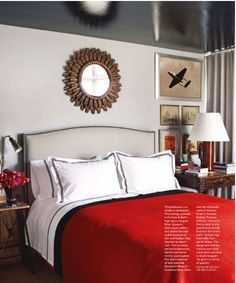 Red comforter with grand embroidered black and white sheets. and the mirror