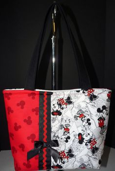Handmade / 3 Inside Pockets  Mickey & Minnie Mouse Purse by Look at Me! Keepsakes  This Mickey & Minnie Mouse handbag can be used as a carry-all or a diaper bag. It is made from an adorable licensed Mickey & Minnie black and white fabric and a red fabric with little mouse heads. It is adorned with a black grosgrain ribbon with red ric-rac and black bow. It has soft fleece pellon so the bag stands on its own. The lining is a double-sided white quilted fabric with three pockets to keep you…
