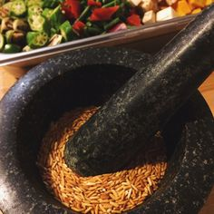 Grind time with the mortar and pestle to make roasted rice powder, a key ingredient  for a very delicious Cambodian stew called Somlaw Kokoe.