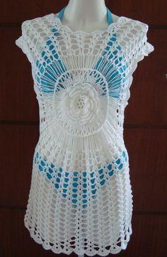 Uma saída de praia em crochê que pode ser usada como vest legging ou blusa alongada. Uma peça moderna,na cor branca com uma flor central dando um belo efeito à peça. Pode ser feita em qualquer cor. R$ 195,00