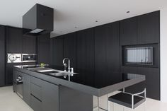 Kitchen design with black wood cabinets and high-gloss center prepping area.