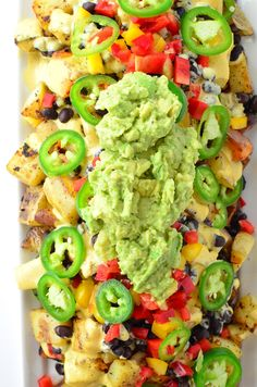 Vegan Potato Nachos! Crispy potatoes piled high with dairy-free cheese sauce, peppers, black beans, and guac! Gluten-Free and Vegan | www.delishknowledge.com