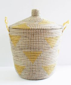 A must-have for every home, this yellow teepee storage basket will add a pop of color and style to any room! Handmade from seagrass, and featuring a pattern of geometric yellow triangles, this storage
