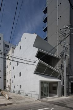 HASE BLDG.8 is a minimalist house located in Aichi, Japan, designed by C+A. This building creates a feeling of chaos in a town of small buildings built on the outskirts of the Osu mall in Nagoya. Approximately 80 square meters take up one floor in this four level volume. Stairs run through these four levels of floors towards the depths of the front road. Every floor is a visual expanse, appearing and disappearing over stairs adjacent to the windows. (2)
