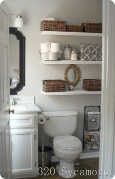 Shelves above toilet with baskets on them for bathroom storage in a tiny bathroom.