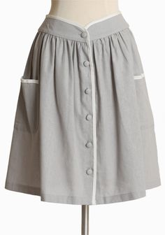 "Bed And Breakfast Pocket Skirt 34.99 at shopruche.com. This woven gray skirt is crafted in a classic A-line silhouette with tonal button closures, contrasting white trim, and side pockets.Self: 55% Linen, 45% Rayon, Contrast: 100% Rayon, Made in USA, 26"" waist, 21"" length from top of waist, *All measurements taken from a size Small"