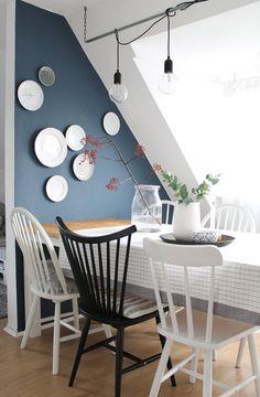 Grande table rectangulaire accolée à un mur bleu nuit très joli + assiettes blanches au mur et chaises à barreaux noir et blanc dépareillées + ampoules nues + nappe à carreaux