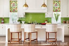 White cabinets and countertops allow the green backsplash to steal the show in this kitchen. - Traditional Home ® / Photo: Lisa Mowry / Design: Katie Rosenfeld