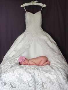 This is a gorgeous newborn photo. I love that the mom's wedding gown is the back drop for her daughter's photo. So beautiful! Newborn photography | baby girl