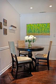 HGTV's Buying and Selling transformed this breakfast room with a cottage-style makeover complete with a beadboard accent wall. White chair rail helps to dress up the nook featuring a small round dining table and two-toned dining chairs.
