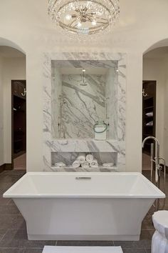 Stunning bathroom with marble clad window looking through to a marble tiled walk-in shower with rainfall shower head.
