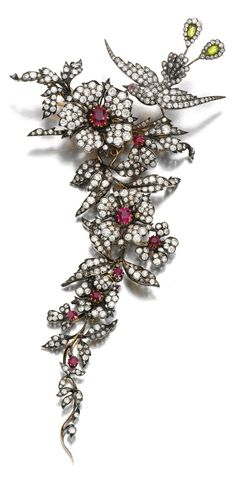 An Antique Ruby and Diamond devant de corsage, Late 19th Century. Designed as an articulated foliate spray surmounted by a bird of paradise, set with circular-cut and cushion-shaped rubies, one synthetic ruby, pear-shaped peridots, circular-cut and rose diamonds, detaches into four brooches. #antique #corsage